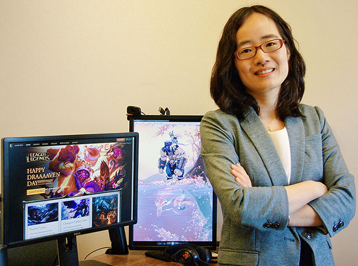 A smiling Cindy Shen standing with arms crossed near two computer screens showing video game images.