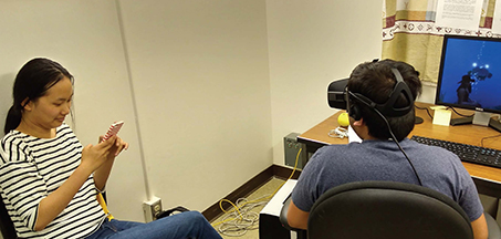 two students, one holding a cell phone and one wearing a virtual reality headset